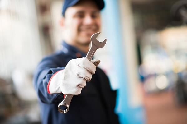 Imagem mostra um mecânico, de uma oficina de caminhões, com sua ferramenta em primeiro plano e o restante da imagem desfocado.